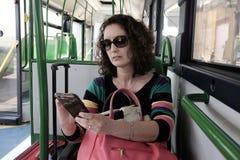 женщина смотрит smartphone на шине Стоковые Изображения RF