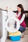 Женщина смотря белизну одевает около стиральной машины Стоковое фото RF