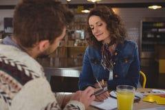 Женщина смотря бизнесмена с таблеткой в кафе Стоковое Фото