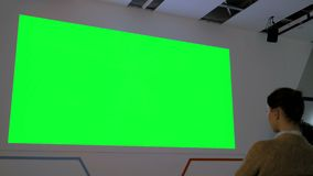 Женщина смотря большой пустой зеленый экран - насмешку кино вверх акции видеоматериалы