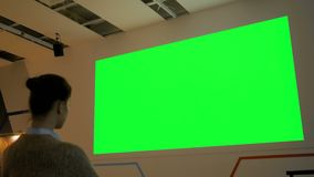 Женщина смотря большой пустой зеленый экран - насмешку кино вверх сток-видео