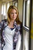 Женщина смотря вне усмехаться окна поезда Стоковая Фотография