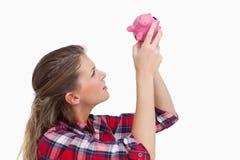 Женщина смотря внутри piggy банка Стоковое Изображение RF