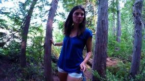 Женщина смотря вокруг пока идущ в лес 4k акции видеоматериалы