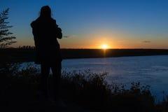 Женщина смотря восход солнца Стоковые Изображения