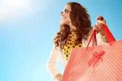 Женщина смотря в расстояние с хозяйственными сумками против голубого неба Стоковые Изображения