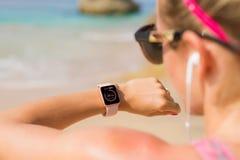 Женщина смотря ее данные по тарифа сердца на smartwatch стоковые изображения
