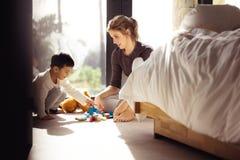 Женщина смотря ее сына играя блоки внутри помещения стоковое фото rf