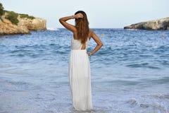 Женщина смотря заботливую на море воду в летнем отпуске наслаждаясь каникулами ослабила нося белое платье пляжа Стоковые Изображения