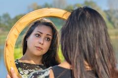 Женщина смотря зеркало в природе стоковые фото
