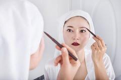 Женщина смотря зеркало и используя бровь состава карандаша Стоковая Фотография