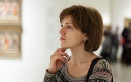 Женщина смотря изображения в художественной галерее стоковое изображение