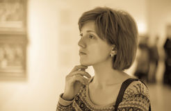 Женщина смотря изображения в художественной галерее стоковые изображения