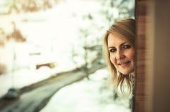 Женщина смотря из окна стоковая фотография