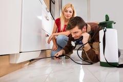 Женщина смотря инсектицид мужского работника распыляя Стоковые Фото