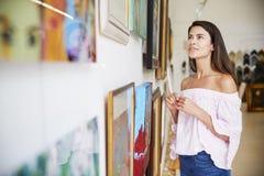 Женщина смотря картины в художественной галерее стоковое изображение