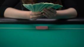 Женщина смотря карточки и кладя доллары на таблицу казино, расточительствуя деньги видеоматериал