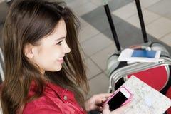 Женщина смотря карту и телефонный номер Она изучает трассу Конец-вверх Стоковая Фотография