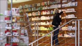 Женщина смотря косметики в супермаркете акции видеоматериалы