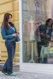 Женщина смотря к окну витрины или магазина стоковое изображение