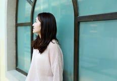 Женщина смотря магазин сидит перед окном и остатками Стоковые Фото