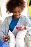 Женщина смотря мобильный телефон и наслаждаясь бокалом вина Стоковая Фотография
