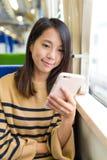 Женщина смотря мобильный телефон на поезде Стоковое Изображение