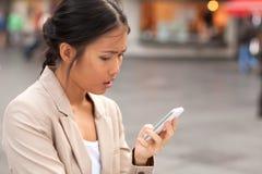 Женщина смотря мобильный телефон Стоковое Изображение RF
