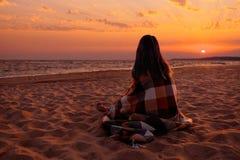 Женщина смотря на заходе солнца над морем стоковые изображения rf