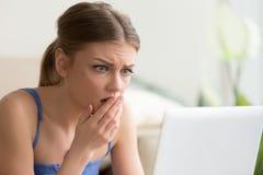 Женщина смотря на экране компьтер-книжки с страхом стоковая фотография rf