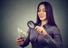 Женщина смотря 100 долларовых банкнот через лупу Стоковое фото RF