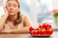 Женщина смотря плиту с томатами но имея чувствительность стоковое фото rf