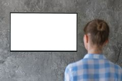 Женщина смотря плоское умное ТВ приведенное с белым ТВ ed пустого экрана с белым пустым экраном - концепцией модель-макета стоковые фото