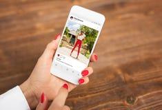 Женщина смотря публично, который делят фото на социальной сети стоковое изображение