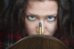 Женщина смотря пулю оружи стоковые фото