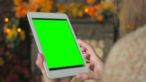 Женщина смотря планшет с зеленым экраном Стоковое Изображение RF
