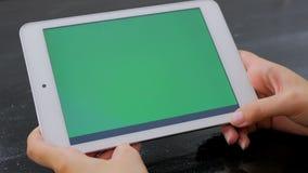 Женщина смотря планшет с зеленым экраном Стоковое Фото