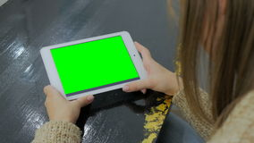 Женщина смотря планшет с зеленым экраном Стоковая Фотография