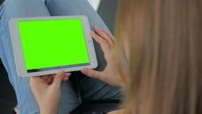 Женщина смотря планшет с зеленым экраном Стоковые Фото