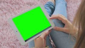 Женщина смотря планшет с зеленым экраном Стоковые Изображения