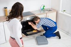 Женщина смотря работника ремонтируя печь Стоковое Изображение RF