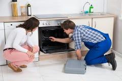 Женщина смотря работника ремонтируя печь Стоковое фото RF