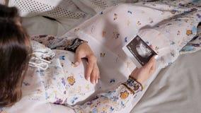 Женщина смотря развертку с младенцем сток-видео