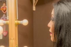 Женщина смотря себя в зеркале после профессионального макияжа стоковые изображения rf
