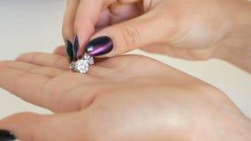 Женщина смотря серьги с диамантами на ее руках в ювелирном магазине дама пробуя на некоторой драгоценности на бутике акции видеоматериалы