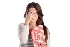 Женщина смотря страшное кино и есть попкорн Стоковые Изображения