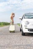 Женщина смотря сломанный вниз с автомобиля пока вытягивающ багаж на проселочной дороге Стоковые Изображения RF
