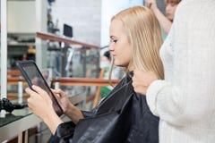Женщина смотря таблетку цифров Стоковое фото RF