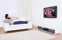 Женщина смотря ТВ пока ослабляющ на софе стоковые изображения