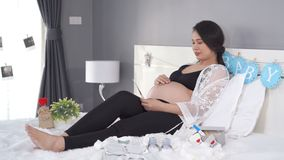 Женщина смотря фото и Пэт ультразвука ее беременный живот на кровати сток-видео